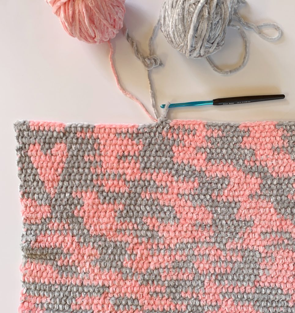 work in progress of improv crochet in pink and grey velvet. It looks like camo.